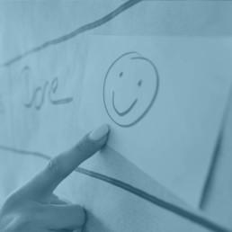 Finger zeigt auf Smiley an Pinnwand