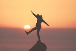 Person balanciert auf Stein vor Sonnenuntergang