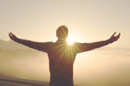 Mann mit ausbgebreiteten Armen vor Sonnenaufgang